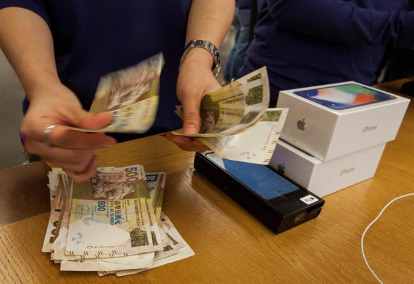 Un empleado de Apple cuenta el dinero de un cliente que pagó por un ejemplar del nuevo iPhone X en una tienda Apple de Hong Kong (China)