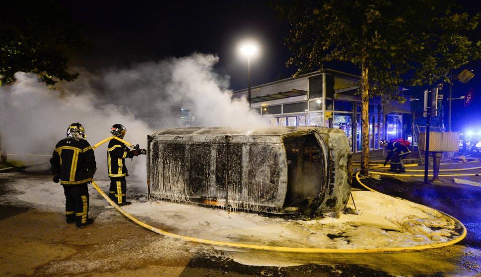 Bomberos trabajan en la extinción de un incendio en un vehículo durante unos disturbios en Nantes (Francia) el 3 de julio de 2018 (EFE/ Franck Dubray)