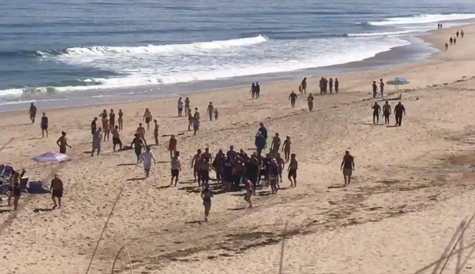 Un grupo de personas ayudan a llevar a la ambulancia a la víctima del ataque de un tiburón en Newcomb Hollow Beach. (Crédito de la imagen: Andrew Jacob / Twitter)