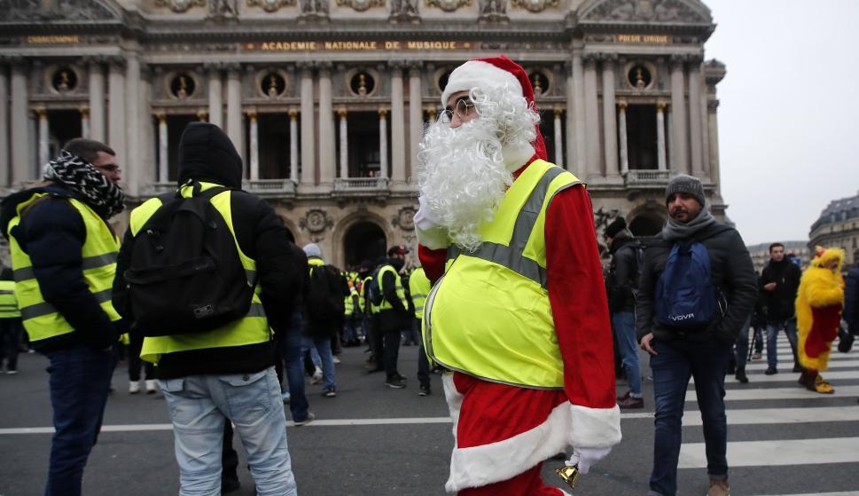 """Un manifestante """"chaleco amarillo"""" que viste un traje de Papá Noel asiste a una manifestación frente a la Ópera en París, Francia, el 15 de diciembre de 2018. (EFE/EPA/IAN LANGSDON)"""