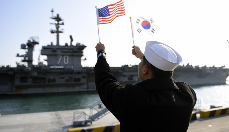 Un marinero de la República de Corea (ROK) ondea banderas al paso del portaaviones de la clase Nimitz USS Carl Vinson (Foto: MC2 Jermaine M. Ralliford)