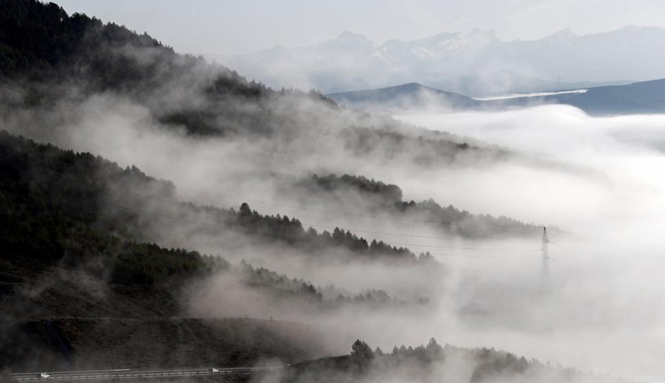 Dos vehículos circulan por la A-21 donde bancos de niebla la cubrían parcialmente a primeras horas de la mañana. ( EFE/ Jesus Diges)