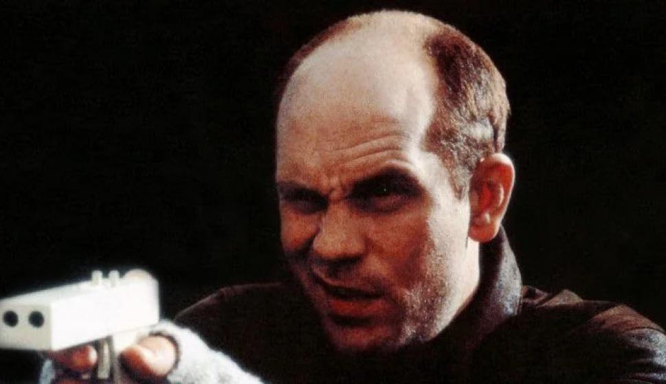"""John Malkovich probando su pistola de plástico en la película """"En la línea de fuego"""". /Columbia Pictures"""