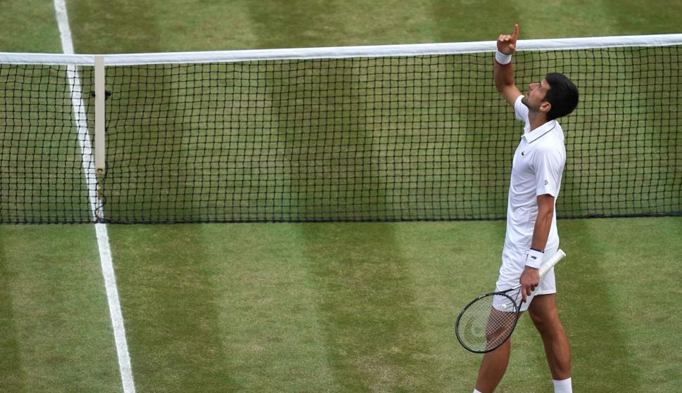 Novak Djokovic levanta el brazo al cielo tras vencer en la final de Wimbledon a Roger Federer. /EFE