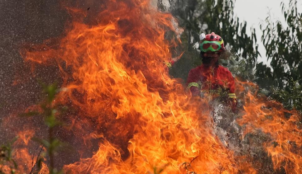 Un bombero trata de extinguir las llamas durante un incendio en Maçao, Portugal. /EFE