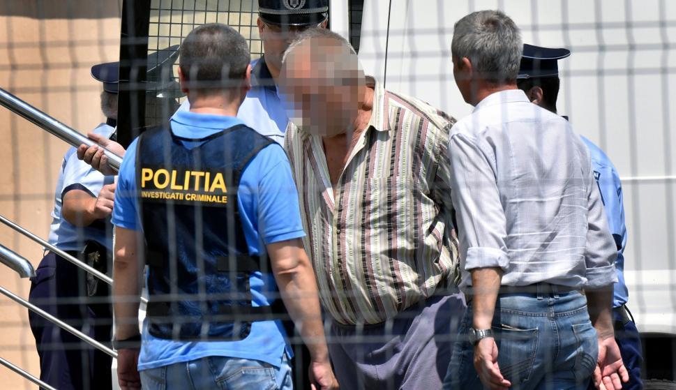 Oficiales de policía escoltan al presunto sospechoso en el tribunal del condado de Dolj, Rumania, el 27 de julio de 2018. /EFE/EPA/BOGDAN DANESCU