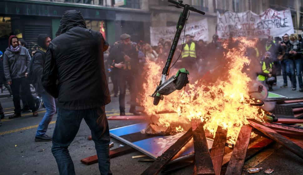 Manifestantes y 'chalecos amarillos' arrojan patinetes a una barricada en llamas durante una manifestación contra las reformas de pensiones. /EFE/EPA