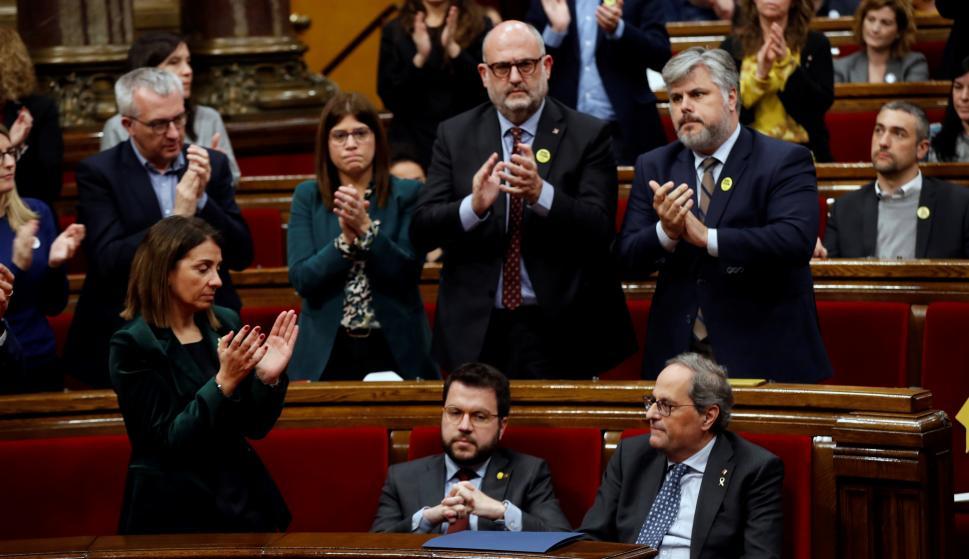 El presidente de la Generalitat, Quim Torra (d), es aplaudido por los miembros de su partido mientras que su vicepresidente, Pere Aragonés (i), y los diputados de ERC permanecen sentados. /EFE