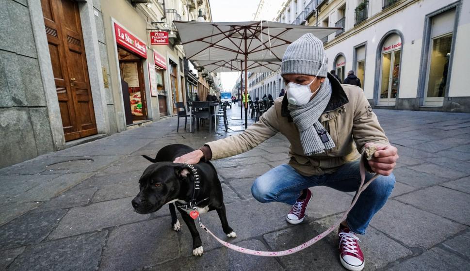 Un hombre con una máscara para protegerse contra el COVID-19 pasea a su perro en Turín, Italia, el 26 de febrero de 2020. /EFE / EPA / Tino Romano