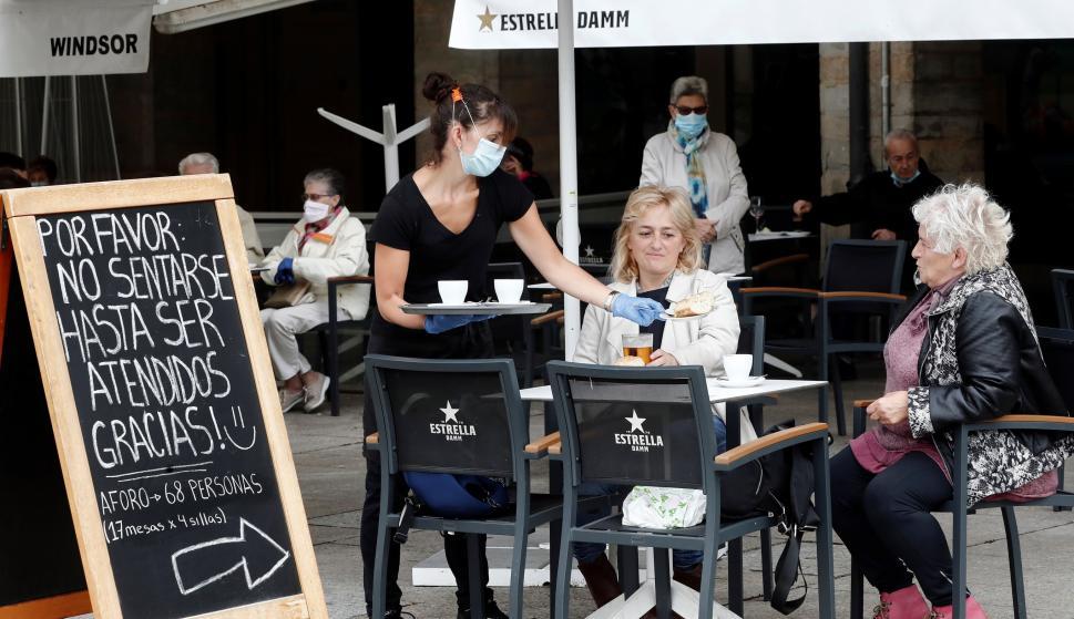 Una camarera atiende a dos clientes en la terraza de un bar de la Plaza del Castillo de Pamplona. /EFE