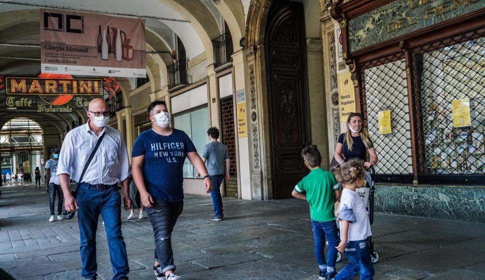 Personas con mascarillas caminan bajo las arcadas de la Piazza San Carlo durante la fase 2 de la emergencia del coronavirus, en Turín, Italia. /EFE