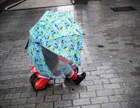 Un niño se refugia del temporal sin dejar la moto de los Reyes