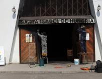 Personas trabajan en la parroquia Santa Isabel de Hungría, donde desconocidos lanzaron en la entrada un paño impregnado con combustible y luego le aplicaron fuego (EFE/Mario Ruiz)
