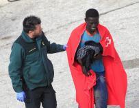 Un agente de la Guardia Civil ayuda a uno de los tres inmigrantes rescatados hoy por Salvamento Marítimo cuando viajaban en una patera en aguas del Estrecho y que han sido trasladados al puerto de Tarifa (Cádiz). EFE/A.Carrasco Ragel