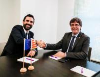 Carles Puigdemont (d) estrecha la mano del presidente del Parlamento autónomo, Roger Torrent, durante su reunión en Bruselas