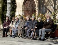 Varios ancianos toman el sol en unos bancos de Olmeda de la Cuesta, Cuenca (EFE/Santiago Torralba)