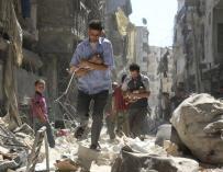Dos hombres sirios mientras rescatan a dos bebés de una zona destruída tras un bombardeo en Alepo