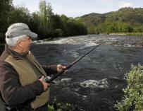 Uno de los cientos de pescadores que han tratado de hacerse en los ríos asturianos con el 'campanu'. EFE