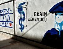 Mural que representa a un encapuchado junto al anagrama de ETA