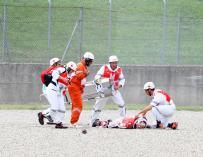 El piloto de prueba del equipo de Moto GP Ducati Michele Pirro (en el suelo) recibe atención médica tras sufrir un accidente en Mugello (EFE/ Claudio Giovannini)
