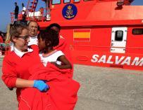 En Tarifa, una voluntaria de Cruz Roja traslada en sus brazos a una niña que viajaba en una de las pateras. EFE/A.Carrasco Ragel.